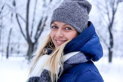 Beautiful winter portrait of young woman in the winter snowy scenery. Beautiful girl in winter clothes. Stock Photo