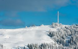 Winter hoar frosting trees,  tower and snowdrifts Carpathian mo. Beautiful winter rime frosting trees, communication tower and snowdrifts on mountain top on blue Stock Image