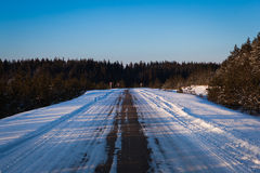 Beautiful winter road through snowy fields,sunset and forests Royalty Free Stock Image