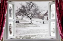 Beautiful winter scene through an open window. View through open window onto a beautiful winter snow street scene in rural England. Red curtains hang in front of Stock Photos