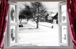 Beautiful winter scene through an open window. View through open window onto a beautiful winter snow street scene in rural England. Red curtains hang in front of Stock Photo