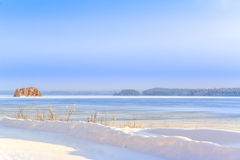 Beautiful winter scene over the frozen lake and a small island Royalty Free Stock Photos
