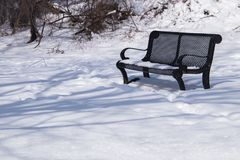 Beautiful snow covered winter scene with  bench. Beautiful winter scene with snow covered ground and bench long shadows Stock Photo