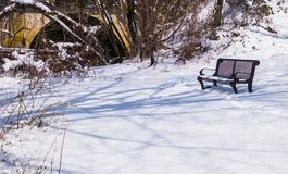 Beautiful snow covered winter scene with  bench. Beautiful winter scene with snow covered ground and bench long shadows Stock Images