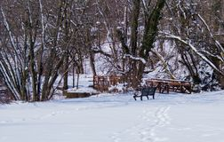 Winter scene with snow bench and bridge. Beautiful winter scene snow covered ground trees in background bench and bridge Royalty Free Stock Image