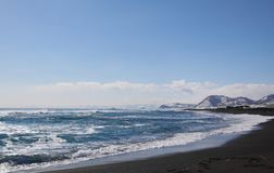 Beautiful winter seascape of Pacific ocean with big waves, black volcano sand and snowy mountains background. Royalty Free Stock Photos