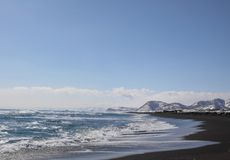 Beautiful winter seascape of Pacific ocean with big waves, black volcano sand and snowy mountains background. Stock Photo