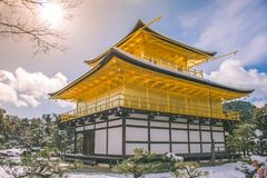 Beautiful winter seasonal of Golden Pavilion of Kinkakuji Temple with white snow falling and blue sky background at Kyoto. Royalty Free Stock Image