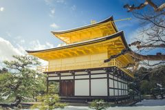 Beautiful winter seasonal of Golden Pavilion of Kinkakuji Temple with white snow falling and blue sky background at Kyoto. Beautiful winter seasonal of Golden Stock Photos