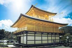 Beautiful winter seasonal of Golden Pavilion of Kinkakuji Temple with white snow falling and blue sky background at Kyoto. Stock Photos