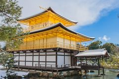 Beautiful winter seasonal of Golden Pavilion of Kinkakuji Temple with white snow falling and blue sky background at Kyoto. Stock Images