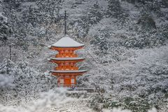 Beautiful winter seasonal of Red Pagoda at Kiyomizu-dera temple surrounded with trees covered white snow background. Royalty Free Stock Photos