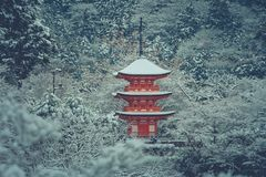 Beautiful winter seasonal of Red Pagoda at Kiyomizu-dera temple surrounded with trees covered white snow background. Royalty Free Stock Images
