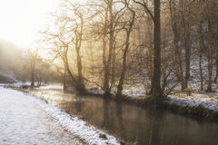 Beautiful Winter snow covered countryside landscape of river flo. Wing with reflections stock photo