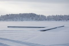Beautiful winter specific photo. Frozen lake at wintertime. Photo with beautiful forest in the background and a dock lying in the. Middle of the lake stock photo