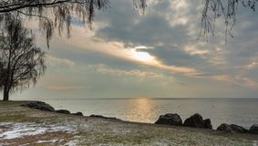 Shore. Lake. Sunrise. Leman. Trees. Stone. Sky. Beautiful winter sunrise on the lake Leman, near the Lausanne city. Winter and snow time royalty free stock image