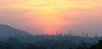 Beautiful winter sunset in India, Orange sky of december dusk. Beautiful winter sunset shot in December, orange sky, mountains and high voltage pole in royalty free stock image