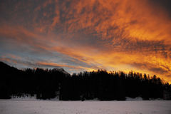 Beautiful winter sunset with orange cloud sky and snow Alps mountains and forest in Engadine region Stock Photo