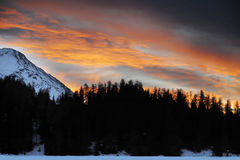 Beautiful winter sunset with orange cloud sky and snow Alps mountains and forest in Engadine region Royalty Free Stock Photo