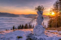 Beautiful winter sunset with snowman in foreground stock images