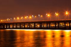 Beautiful winter view of the bridge, lanterns light reflected on the ice of the Dnieper River. Ukraine stock image
