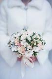Beautiful winter wedding bouquet in hands of bride closeup stock photo