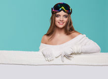 Beautiful winter woman holding a blank billboard  Royalty Free Stock Photography