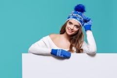 Beautiful winter woman holding a blank billboard  Royalty Free Stock Photo