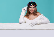 Beautiful winter woman holding a blank billboard isolated. On blue background Royalty Free Stock Photo