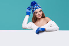 Beautiful winter woman holding a blank billboard isolated. On blue background stock image