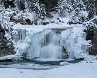 A beautiful wintery waterfall surrounded by snow-covered trees stock image