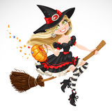Beautiful witch with candy in pumpkin Stock Images