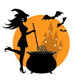 Beautiful witch and cauldron. Beautiful witch prevents potion in a cauldron. In the background the castle Stock Photo
