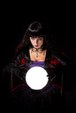 Beautiful witch or fortune teller with a crystal ball royalty free stock photos
