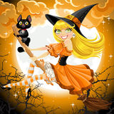 Beautiful witch and her black cat familiar flying  Stock Image