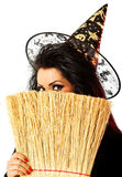 Beautiful witch hiding. Young female dressed up as a witch hiding behind broom Royalty Free Stock Photo