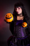 Beautiful witch holding Jack lantern oranges. Selective focus on fruits stock image