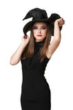 Beautiful witch holds a hat Stock Photo
