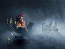 Beautiful witch making witchcraft. Witch conjuring over the smoky background with a castle on a mountain. Halloween concept Royalty Free Stock Photos