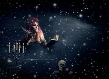 Beautiful witch making witchcraft in the dungeon. Beautiful witch making witchcraft on a snowy winter background Stock Photo