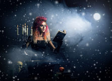 Beautiful witch making the witchcraft in the dungeor. Beautiful witch making witchcraft over winter background Royalty Free Stock Photography