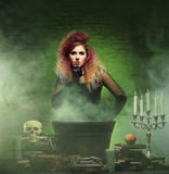 Beautiful witch making witchcraft. Halloween concept: witch conjuring in a dungeon over green background Stock Images
