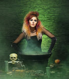 Beautiful witch making witchcraft. Halloween concept: witch conjuring in a dungeon over green background Stock Image