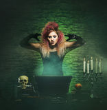 Beautiful witch making witchcraft. Halloween concept: witch conjuring in a dungeon over green background Stock Photography
