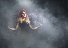 Beautiful witch making the witchcraft over the smoky background. Halloween image Stock Image