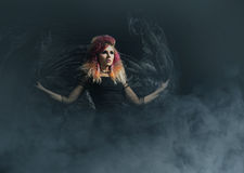 Beautiful witch making the witchcraft over the smoky background. Halloween image Stock Photo