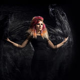 Beautiful witch making the witchcraft over the smoky background. Halloween image Stock Images
