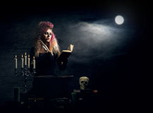 Beautiful witch making witchcraft on a smoky background. Halloween image. Stock Photo