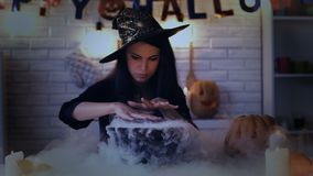 Beautiful witch performing mysterious magic ritual, cooking potion in cauldron. Stock footage stock video footage