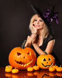 Beautiful witch with pumpkins. Halloween royalty free stock image